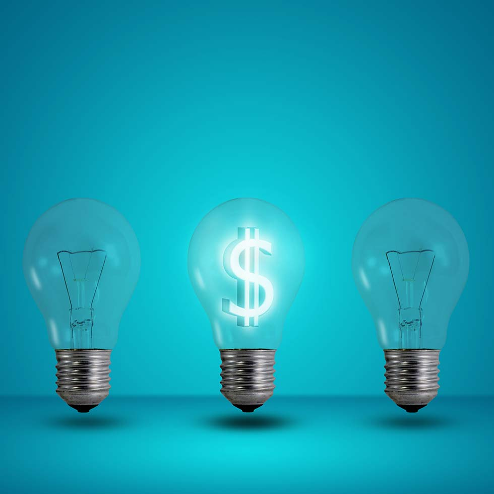 3 Light Bulbs With Middle One Being Lit And Holding A White Dollar Sign Inside